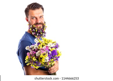 Portrait of a handsome man with flowers in beard holding a bouquet of flowers on white