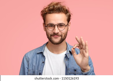 Portrait of handsome man has stubble, makes ok sign, agrees or likes something has joyful expression, poses against pink background, proves everything goes according to plan. Body language concept