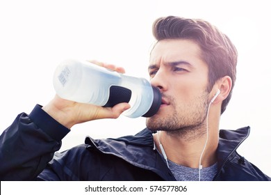 Portrait of a handsome man in headphones drinking water isolated on a white background