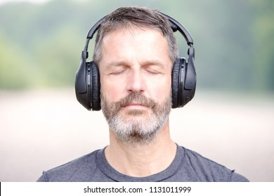 portrait of handsome man with headphones outdoors