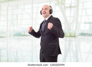 Portrait of handsome man with headphones smiling and dancing on good music, at the office