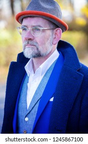 portrait of handsome man in his 50s in blue suit and coat outdoors