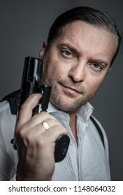 portrait of a handsome man holding a gun