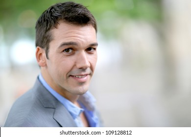 Portrait of handsome man with jacket standing in the street