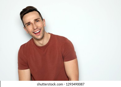 Portrait of handsome man laughing against light background. Space for text