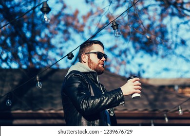 Portrait of a handsome man in leather jacket standing with coffee to go on blue sky background