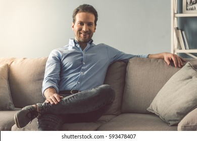 Portrait of handsome man looking at camera and smiling while sitting on couch at home