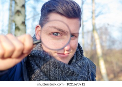 portrait of handsome man looking through a magnifying glass outdoors