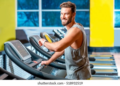Portrait of handsome man making cardio workout on stationary treadmill in the gym.