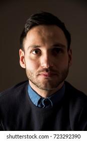 Portrait of a handsome man, pensive expression. Stylish attitude. Businessman with clock. Crestfallen.
