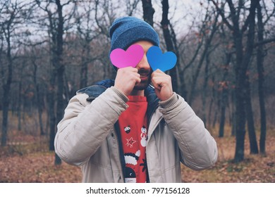 Portrait of handsome man with pink and blue valentines cards. Valentins day. Valentines concept. Man holding hearts in his hands.