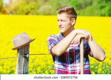 portrait of handsome man with pitchfork standing in front of yellow field