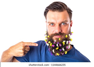 Portrait of a handsome man pointing his beard with flowers on white