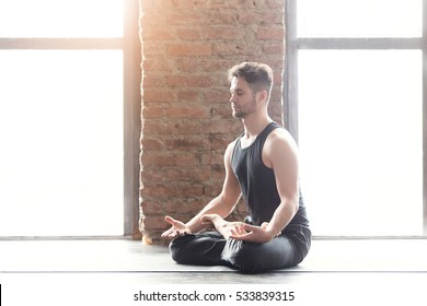 Portrait of a handsome man practicing meditation and yoga against an urban background with picture window and red brick wall on black wooden floor.