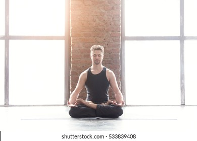 Portrait of a handsome man practicing meditation and yoga against an urban background with picture window and red brick wall on black wooden floor, full length.