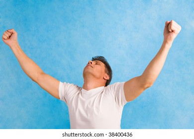 Portrait of handsome man raising his arms over blue background