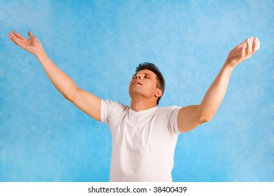 Portrait of handsome man raising his arms in delight over blue background