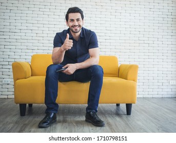 Portrait of handsome man showing thumbs up and smiling at camera.
