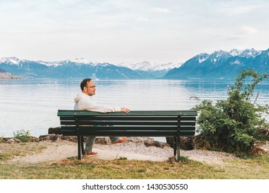 Portrait of handsome man with sitting on bench, meditating by the lake, wearing white sweatshirt