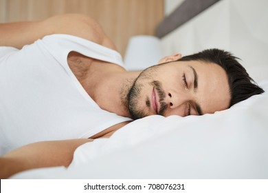 Portrait of a handsome man sleeping in bed