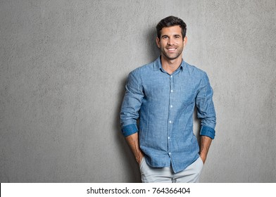 Portrait of a handsome man smiling against grey background with copy space. Smiling latin guy with hands in pocket in blue shirt standing and leaning on wall. Successful hispanic man looking at camera
