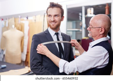 Portrait of handsome man smiling during model fitting of tailored suit in atelier