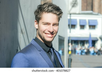 Portrait of a handsome man smiling and wearing a blue suit - Attractive male model