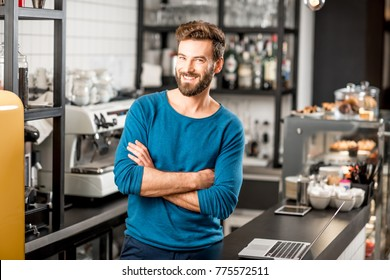 Portrait of a handsome man standing at the bar of the modern cafe interior