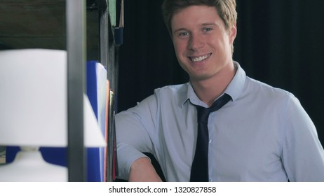 Portrait handsome man standing near bookshelves. Successful young businessman looking at the camera with friendly smile.