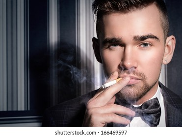 Portrait of a handsome man in a suit with a cigarette