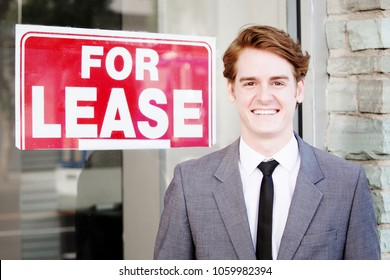 portrait of handsome man in suit standing in front of sign For Lease