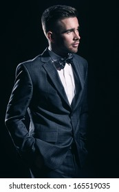 Portrait of a handsome man in a suit who is posing over a black background