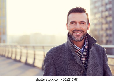 Portrait of handsome man wearing coat during cold winter evening