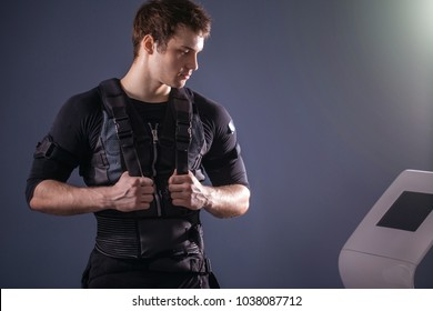 portrait of handsome man wearing ems suit near electro muscle stimulation machine