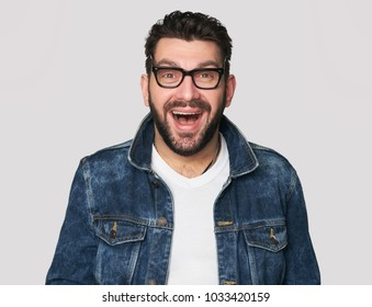 Portrait of a handsome man wearing glasses and denim clothes. Isolated on grey background. Happy guy looking at camera.