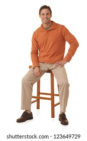 Portrait of a handsome man wearing an orange sweater sitting on a stool isolated on a white background