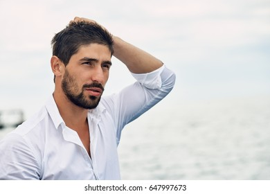 Portrait of a handsome man wearing white shirt. Sea in the background.