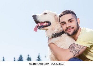 Portrait of a handsome man wearing yellow t-short and jeans with tattoo on his arm sitting on the grass, looking at us smiling and hugging his lovely golden retriever in the park