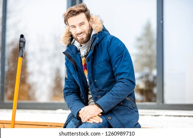 Portrait of a handsome man in winter clothes sitting on the terrace of the modern house