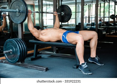 Portrait of a handsome man workout with barbell on bench in fitness gym