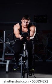 Portrait of a handsome man workout on a fitness on the exercise bike on a dark background at gym.