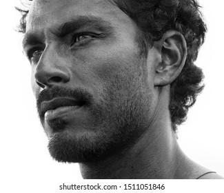 Portrait of handsome masculine guy with facial hair and black hair is highlighted with strong features and firm posture