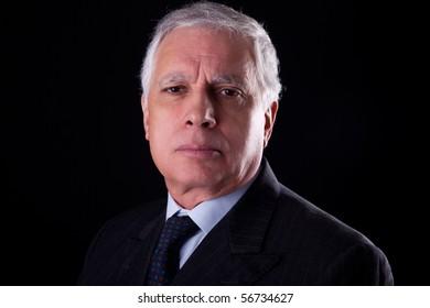 Portrait of a handsome mature businessman,  on black background, studio shot