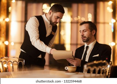 Portrait of handsome mature businessman reading menu in luxury restaurant talking to waiter, copy space