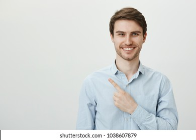 Portrait of handsome mature caucasian male entrepreneur pointing left with index finger while looking with confident bright smile at camera, being assured in his company successful deals