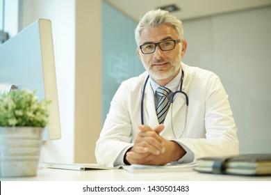 Portrait of handsome mature doctor sitting at desk in modern office