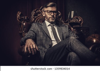 A portrait of a handsome mature man in a formal costume aitting in the armchair in the classic interior. Men's beauty, fashion.