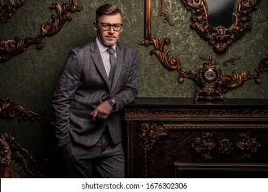 A portrait of a handsome mature man in a formal costume posing in the classic interior. Men's beauty, fashion.