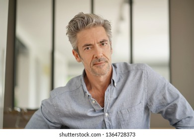 Portrait of handsome mature man looking at camera in contemporary home