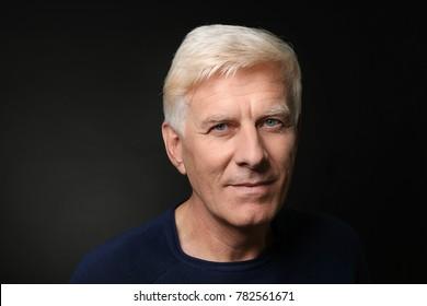 Portrait of handsome mature man on dark background